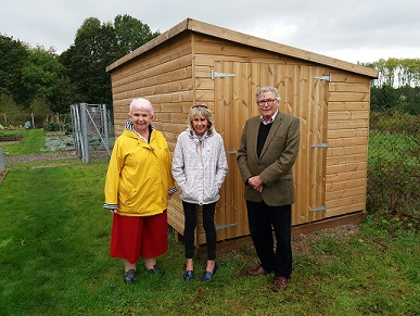 Cllrs Balfour, Barker and Colman standing by shed at allotment site